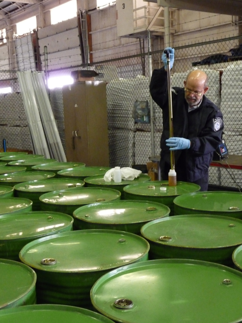 A Customs and Border Patrol agent in a Tacoma, Wash. warehouse draws samples of Chinese honey that is being shipped to Chicago.  (c) Photot by a. schneider